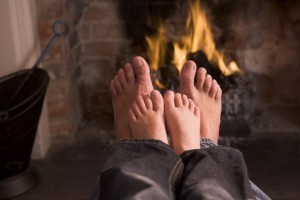 Father and son's Feet warming at a fireplace